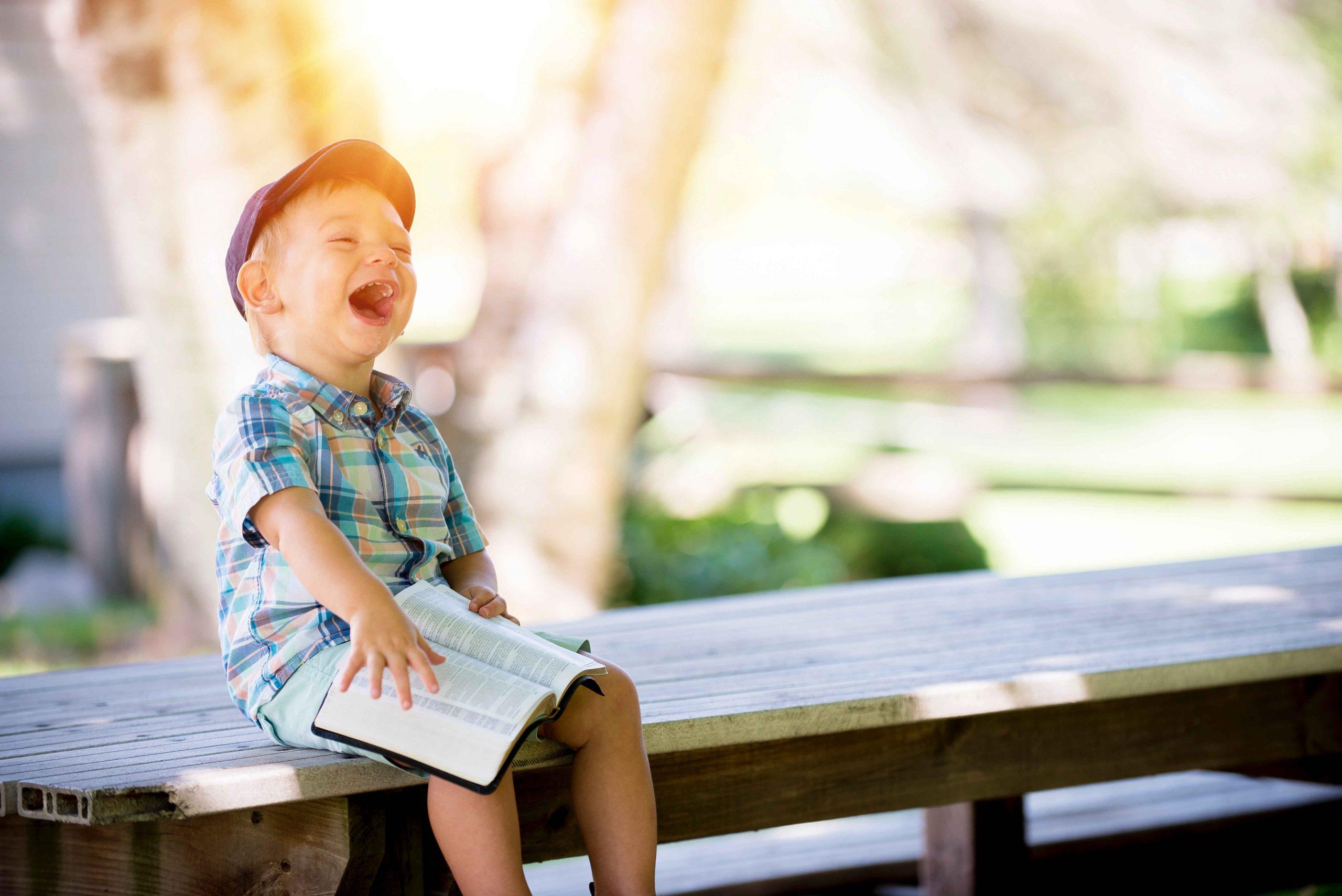 menino lindo com um livro no colo feliz