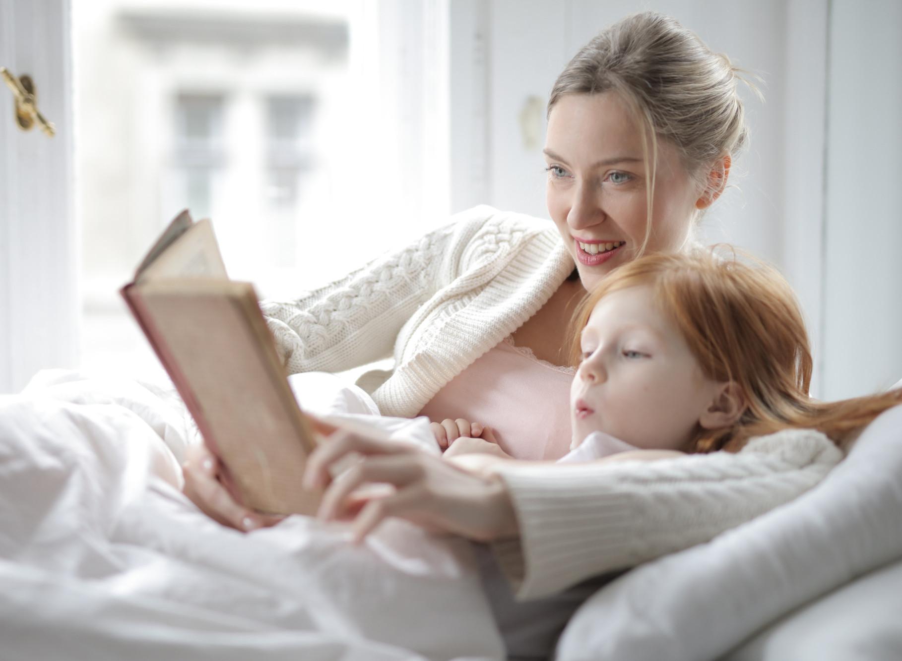 mulher segurando livro para uma criança que está lendo